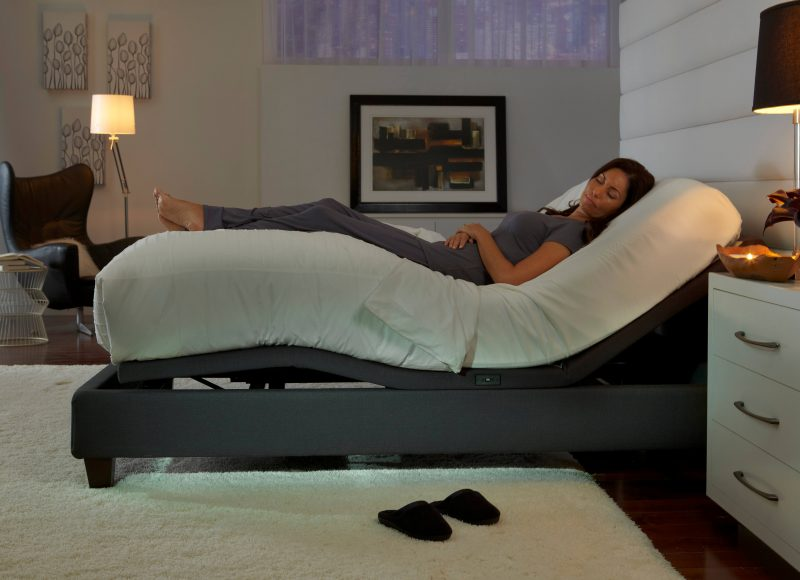 woman sleeping with legs elevated on adjustable bed
