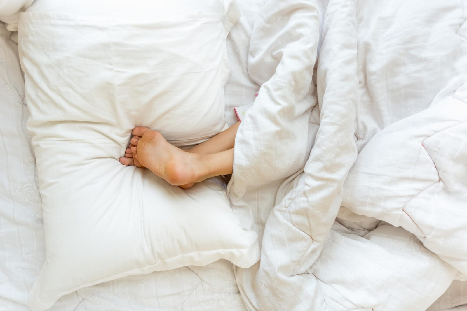 woman sleeping with legs elevated on pillow